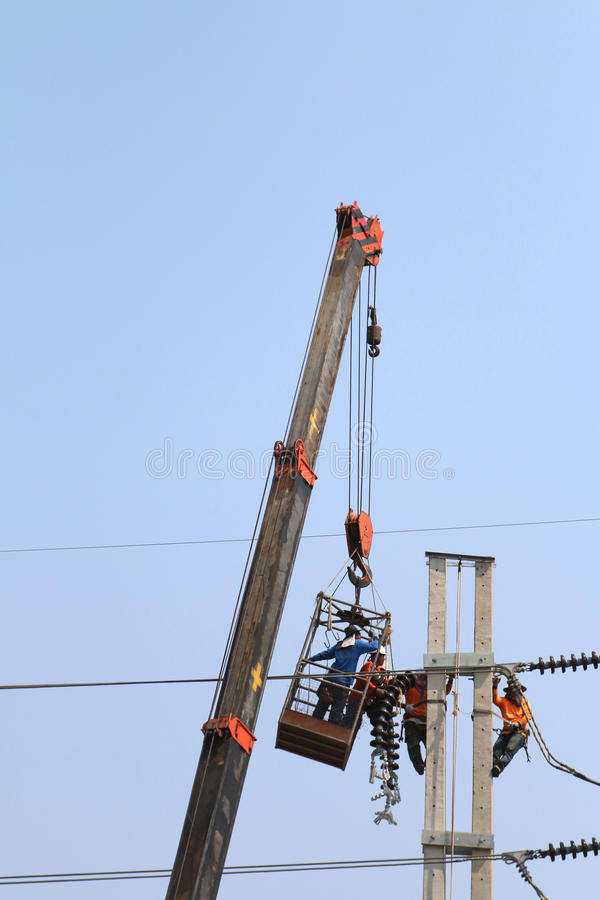 Electrician working at height by connect a high voltage wire royalty free stock photo