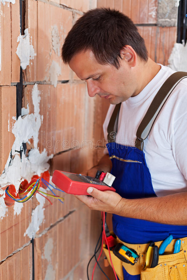 Electrician working inside new building checking wires royalty free stock photography
