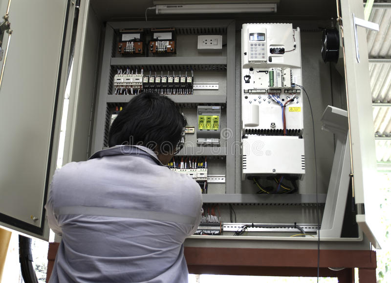 Electrician working. One electrician working on a industrial panel mounting, assembling, adjusting new voltage wiring stock photo