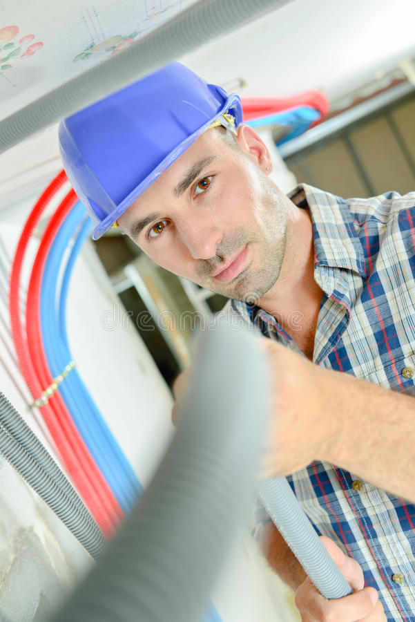 Electrician working through open ceiling hatch royalty free stock image