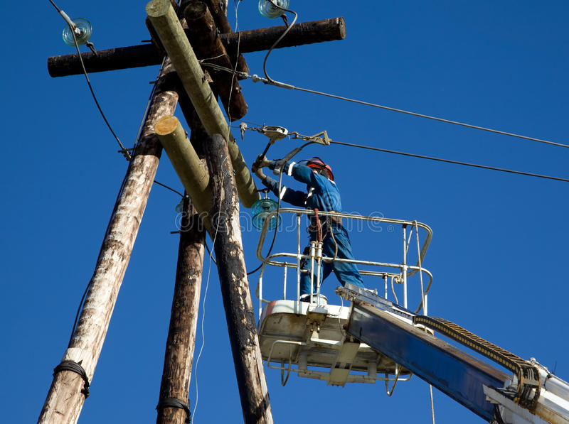 Electrician working on power line pole stock photos