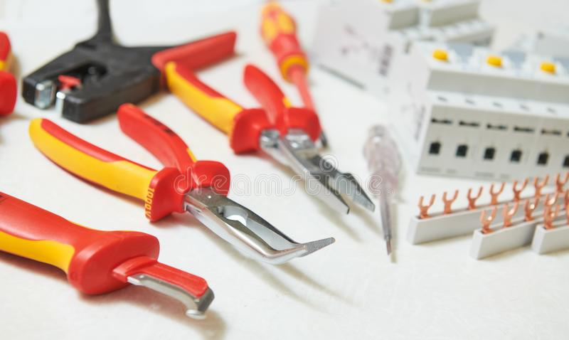 Electrician working tools and circuit breaker before installation in switch box. Electrician working tools. Pliers, stripper, cutter and circuit breaker before royalty free stock images