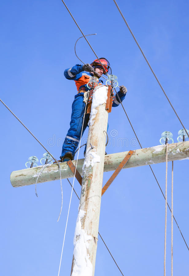 Electrician working on top of an electricity pylon stock image