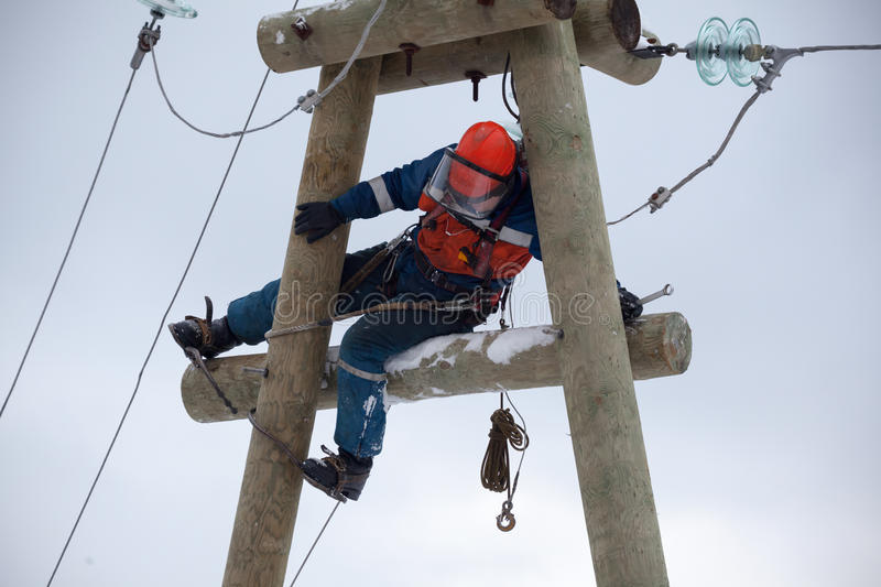 Electrician working on top of an electricity pylon royalty free stock images