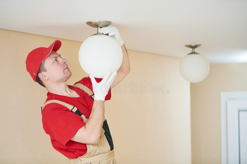 Electrician works with ceiling lamp. installing or repair service royalty free stock photos