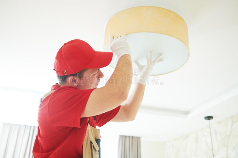 Electrician works with ceiling lamp. installing or repair service stock images