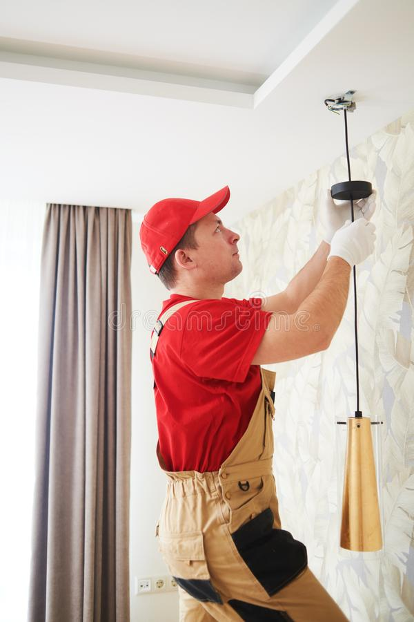 Electrician works with ceiling lamp. installing or repair service royalty free stock photo