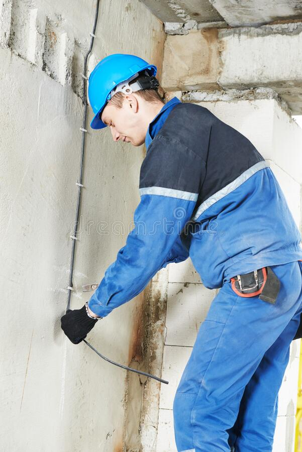 Electrician works with electric cable. Laying it in the hole stock photos