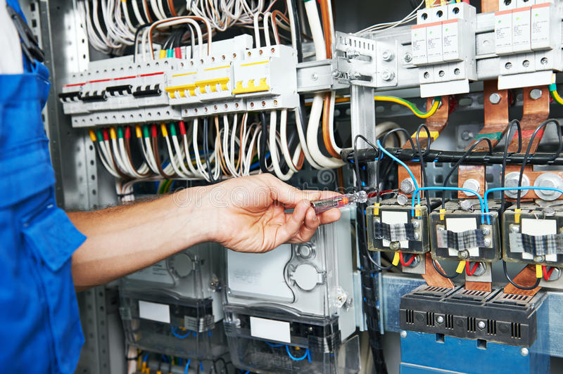 Electrician works with electric meter tester in fuse box stock photos