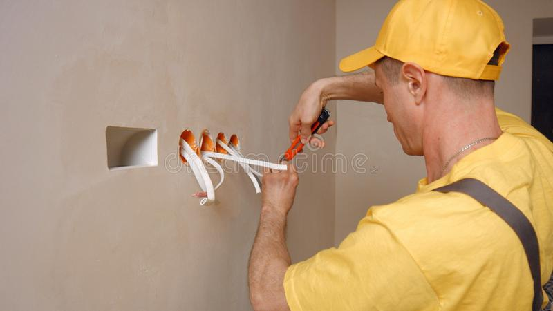 Electrician works with electric wires in new apartment. royalty free stock photo