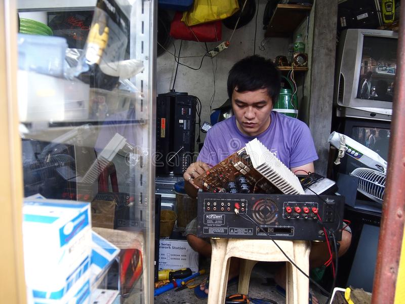 An Electrician Works On A Household Appliance Inside His Repair Shop ...
