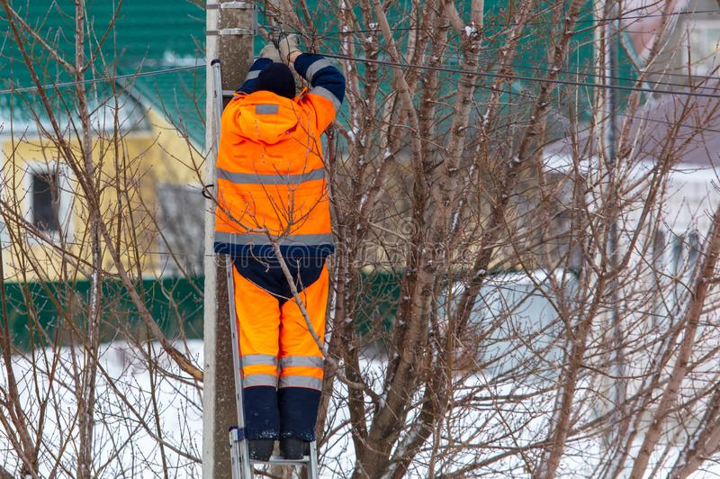 Electrician works on a pole in winter stock photography