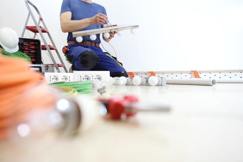Electrician works with screwdriver installs the lamps, house electric circuits, electrical wiring royalty free stock photo