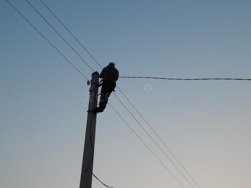 Electrician works in special clothes on the pole stock image
