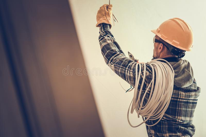 Electrician at Work. Electrician in Yellow Hard Hat with Cable Working in the Construction Area royalty free stock photography