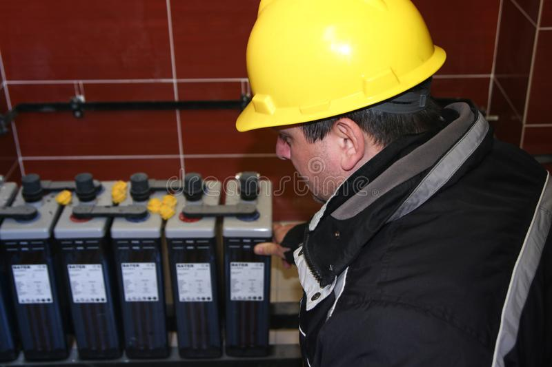 Electrician with yellow helmet check accumulator. Electrician with yellow helmet check battery pack stock photos