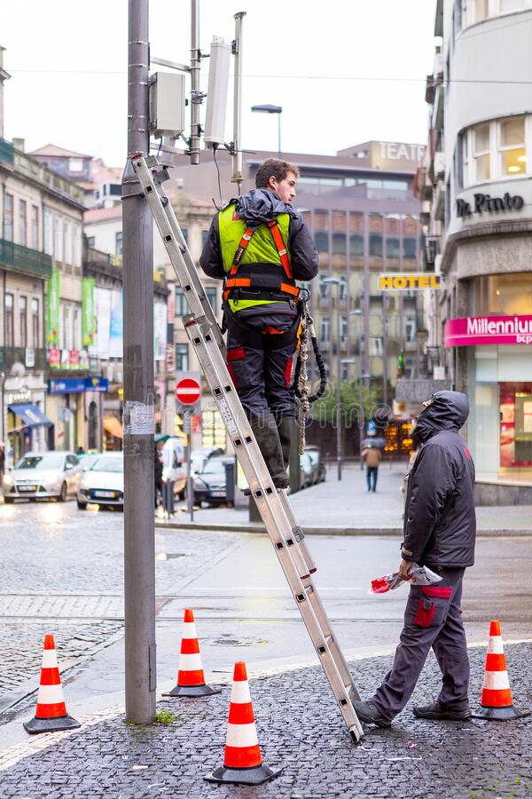 Electricians repairing an energy malfunction on a traffic light pole stock image