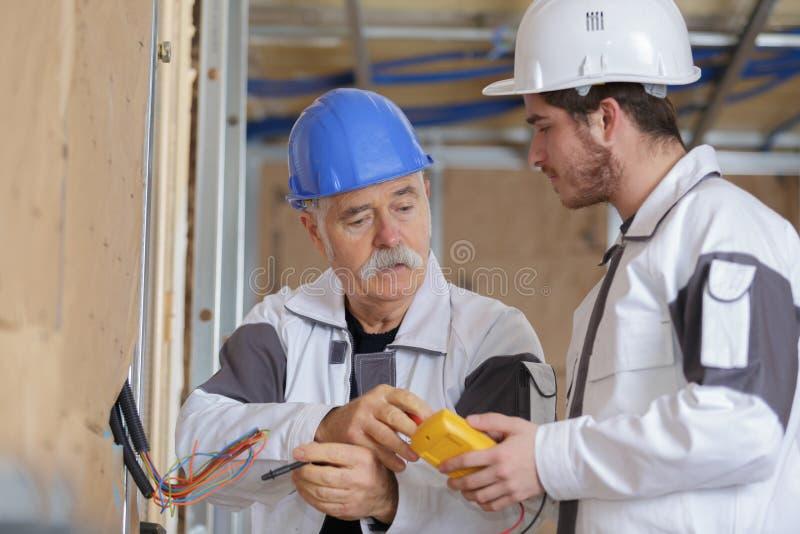 Electricista With Apprentice Working en nuevo hogar imagen de archivo