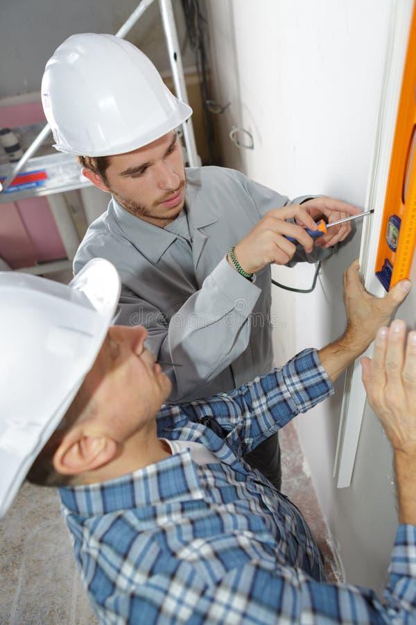 Electricista With Apprentice Working en nuevo hogar fotografía de archivo libre de regalías