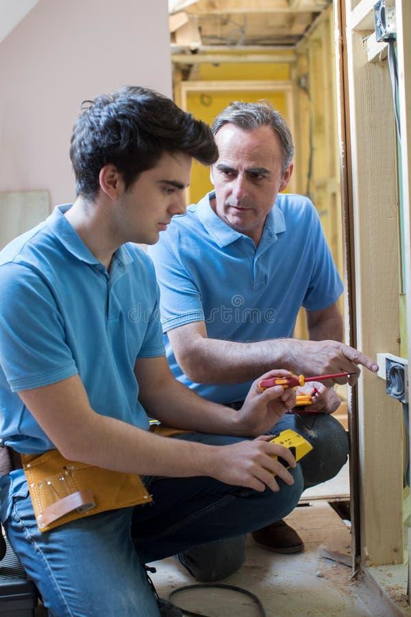 Electricista With Apprentice Working en nuevo hogar fotos de archivo