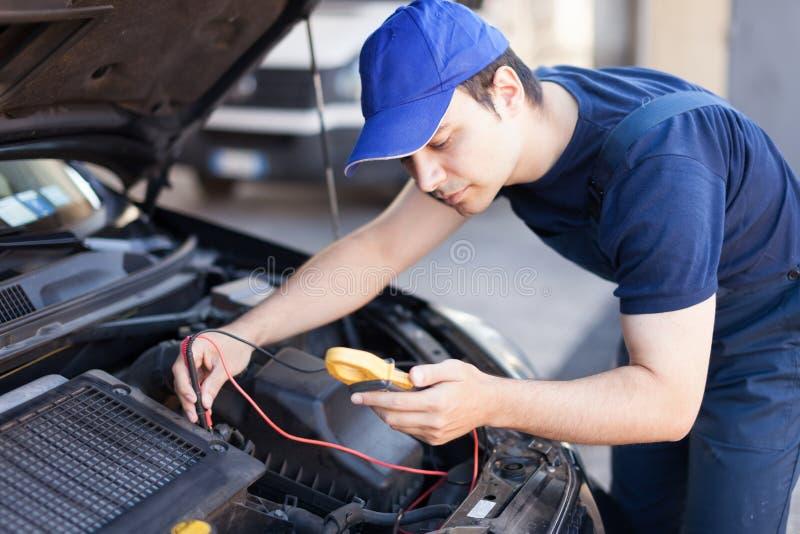 Electricista auto que trabaja en un motor de coche imagen de archivo