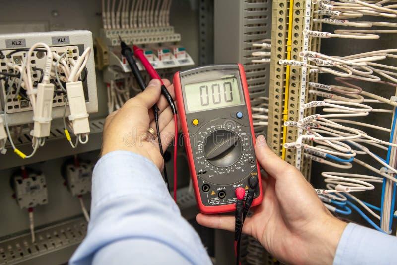 Electricista con el probador del multímetro en manos imagen de archivo
