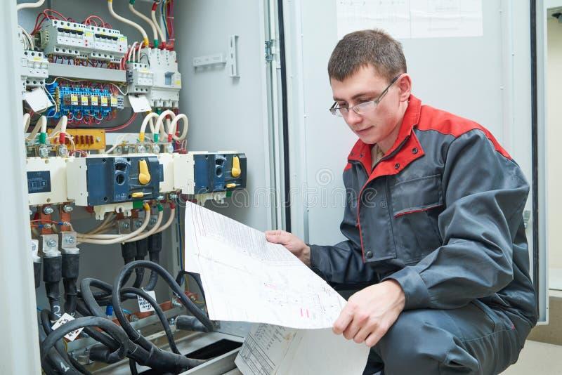 Electricista con proyecto eléctrico del esquema imagen de archivo