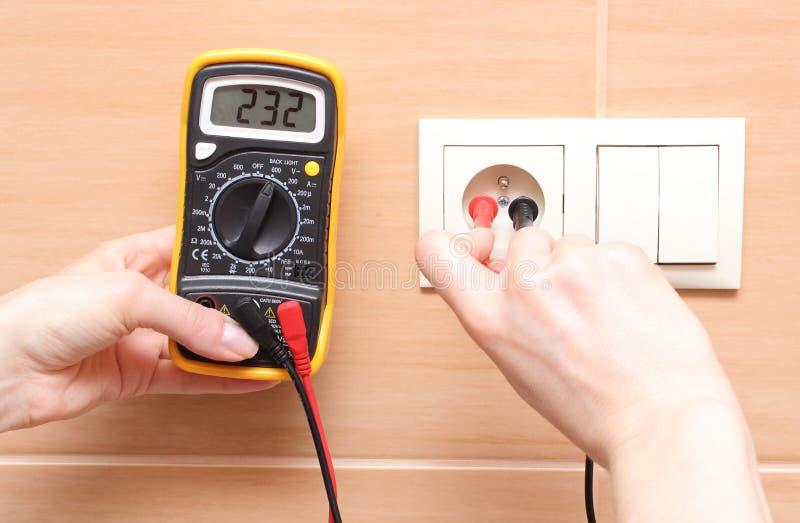 Electricista de la mano que comprueba voltaje imagen de archivo libre de regalías