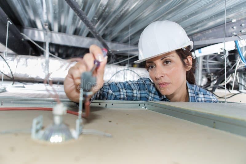 Electricista de sexo femenino que trabaja en spotlamp desde arriba fotografía de archivo