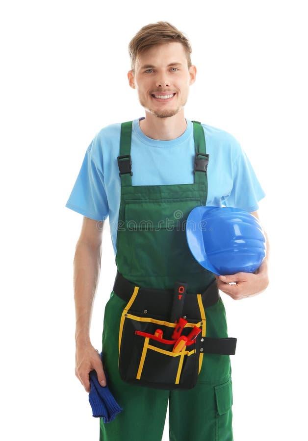Electricista de sexo masculino joven con el casco de protección en el fondo blanco imagen de archivo