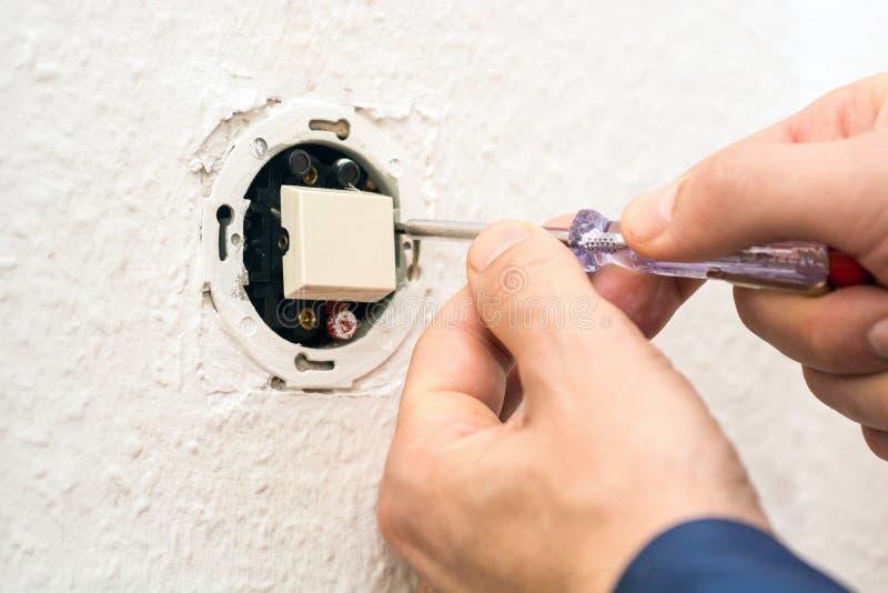 Electricista de sexo masculino que repara el interruptor eléctrico imagenes de archivo