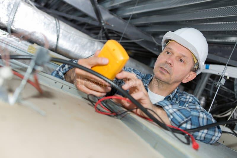 Electricista de sexo masculino que repara el sensor del fuego foto de archivo