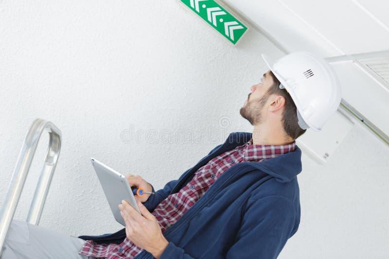 Electricista de trabajo duro que sube en escalera imágenes de archivo libres de regalías