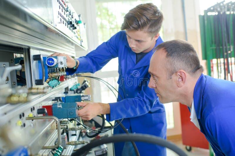 Electricista del aprendiz bajo supervisión imagen de archivo libre de regalías