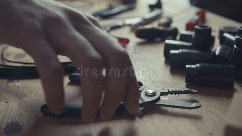 Electricista del artesano que trabaja en el cableado usando pares de alicates para pelar fotografía de archivo