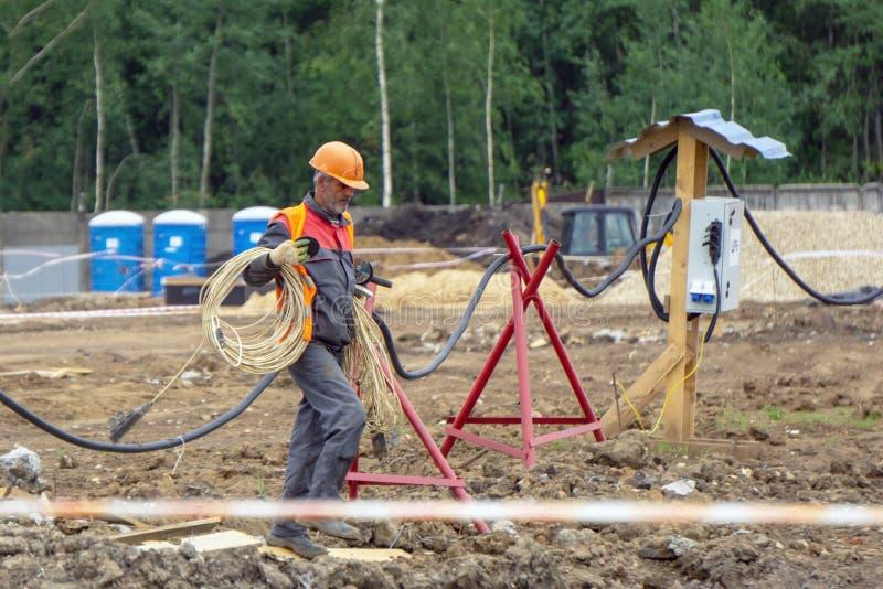 Electricista en el emplazamiento de la obra para conectar un cable eléctrico foto de archivo libre de regalías