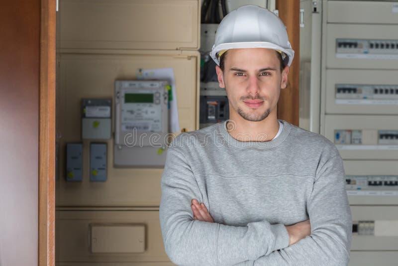 Electricista joven que presenta los brazos cruzados en el lugar de trabajo fotografía de archivo