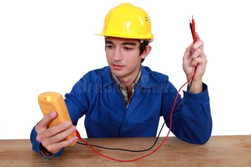 Electricista que usa el probador fotos de archivo