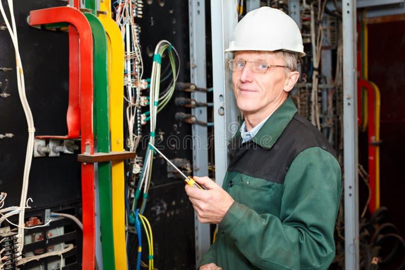 Electricista maduro que trabaja en sombrero duro con los cables imagenes de archivo