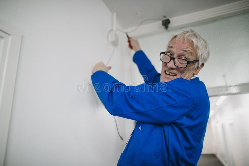 Electricista mayor Fitting una cámara de Secuirty imagen de archivo libre de regalías