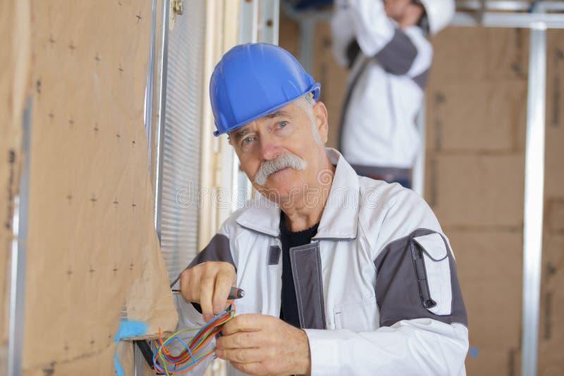 Electricista mayor que trabaja con los alambres en el nuevo apartamento imagenes de archivo