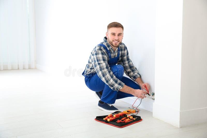 Electricista profesional con el probador que comprueba voltaje dentro foto de archivo libre de regalías