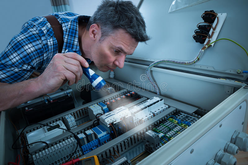 Electricista que analiza el fusebox con la antorcha fotos de archivo libres de regalías