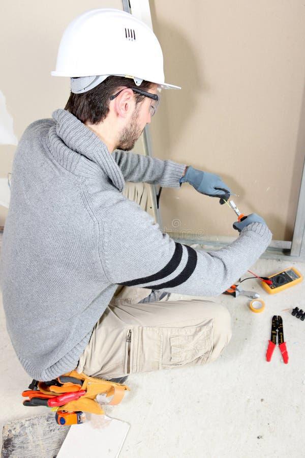 Electricista que ata con alambre un cuarto imagen de archivo libre de regalías