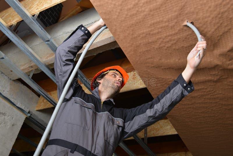 Electricista que cabe un cable foto de archivo