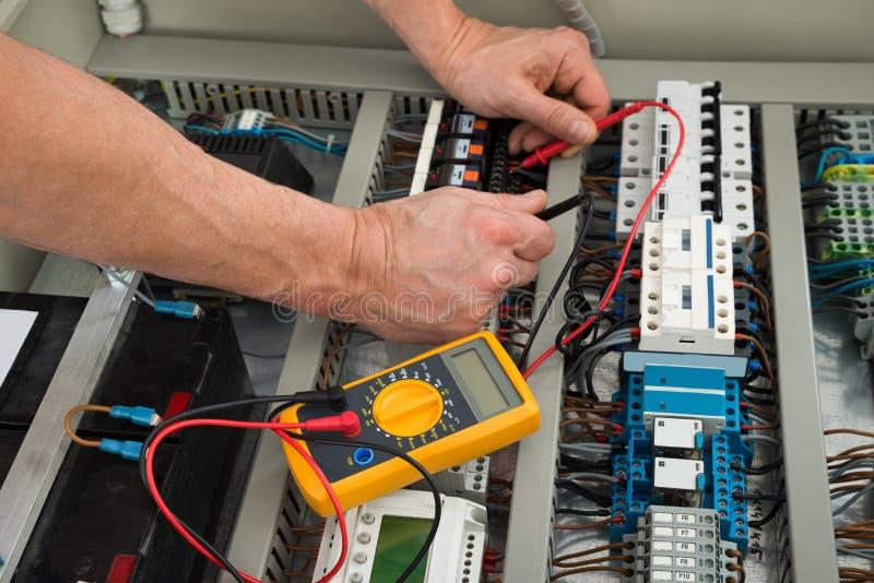 Electricista que comprueba una caja del fusible foto de archivo