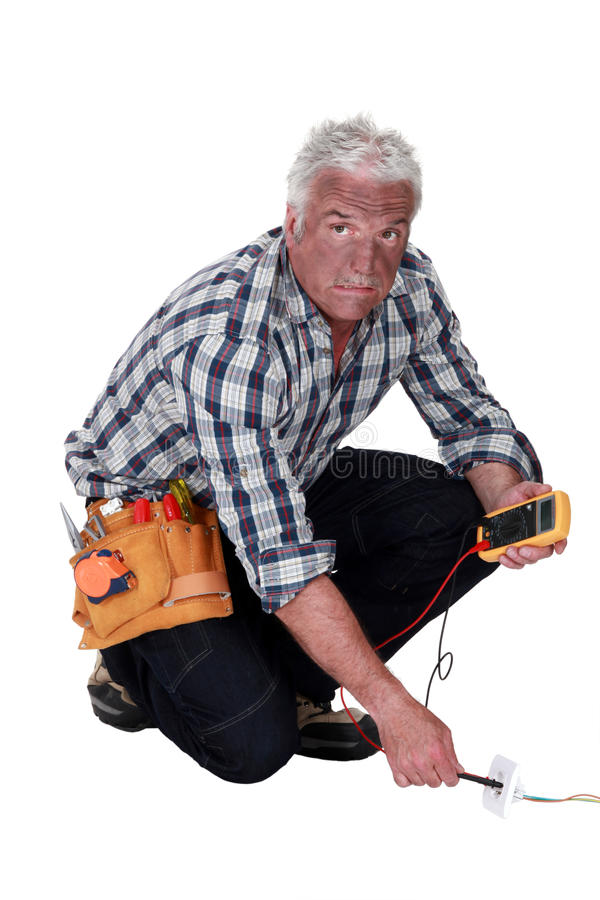 Electricista que comprueba voltaje foto de archivo