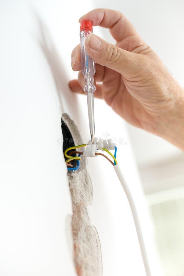 Electricista que comprueba voltaje eléctrico imagenes de archivo