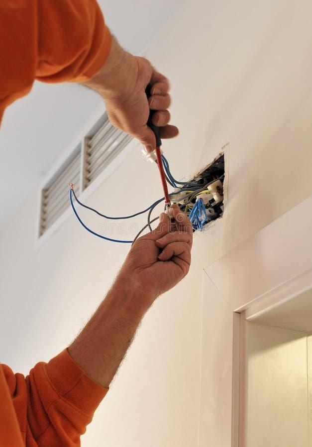 Electricista que conecta el cableado durante la renovación de la casa imagen de archivo