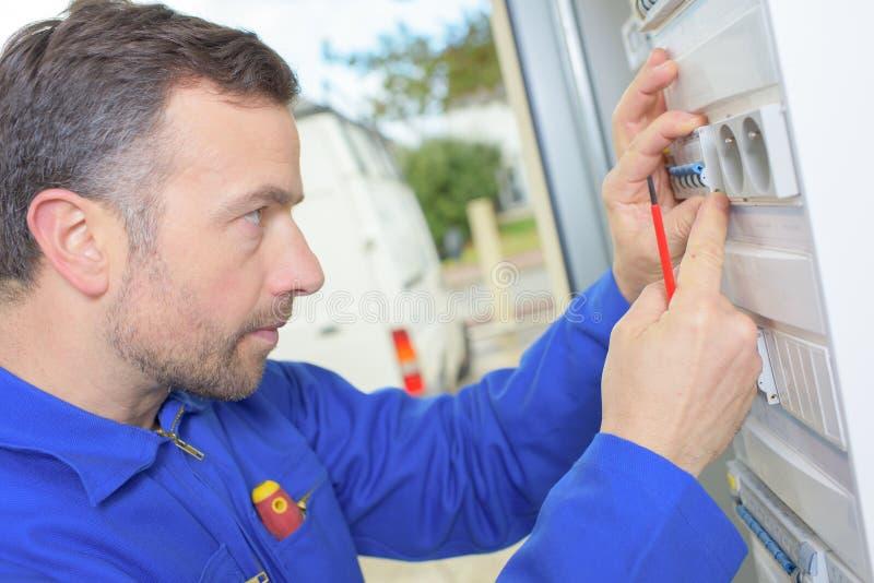 Electricista que examina un fusebox imagenes de archivo